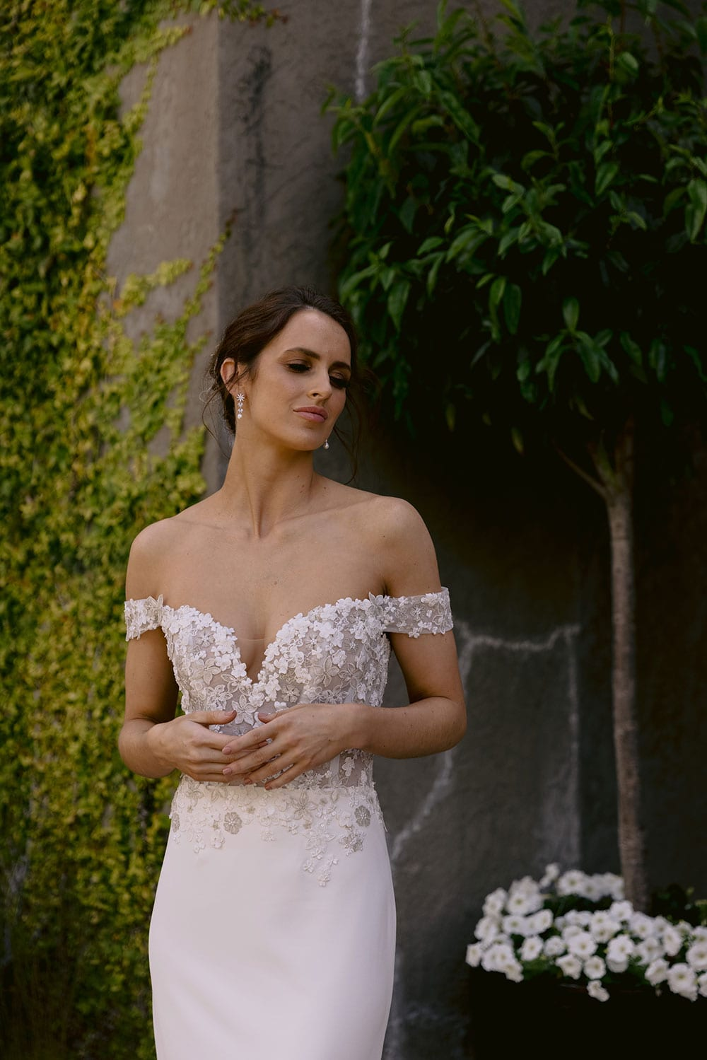 Chloe Wedding gown from Vinka Design - Wedding gown with 3D embellished platinum and ivory flower lace, complemented by stunning off-shoulder straps. A semi-sheer bodice trails into a gorgeous stretch crepe skirt that hugs the figure in all the right places. Model wearing gown in gardens detail of V front of dress.