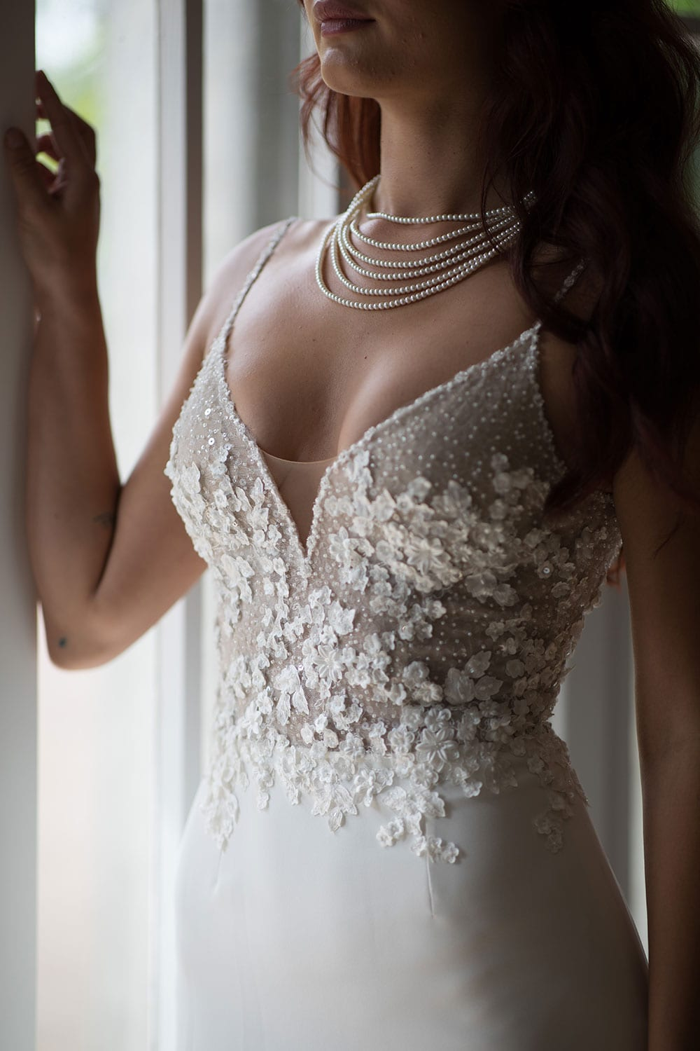 Azure Wedding Gown from Vinka Design - Elegantly tailored trouser combined with a beautiful lace blouse for the Modern Bride. The blouse features a high neck and low back, with in-built camisole, fitted sleeves, & pearl buttons. Model wearing gown , close up of bodice detail.