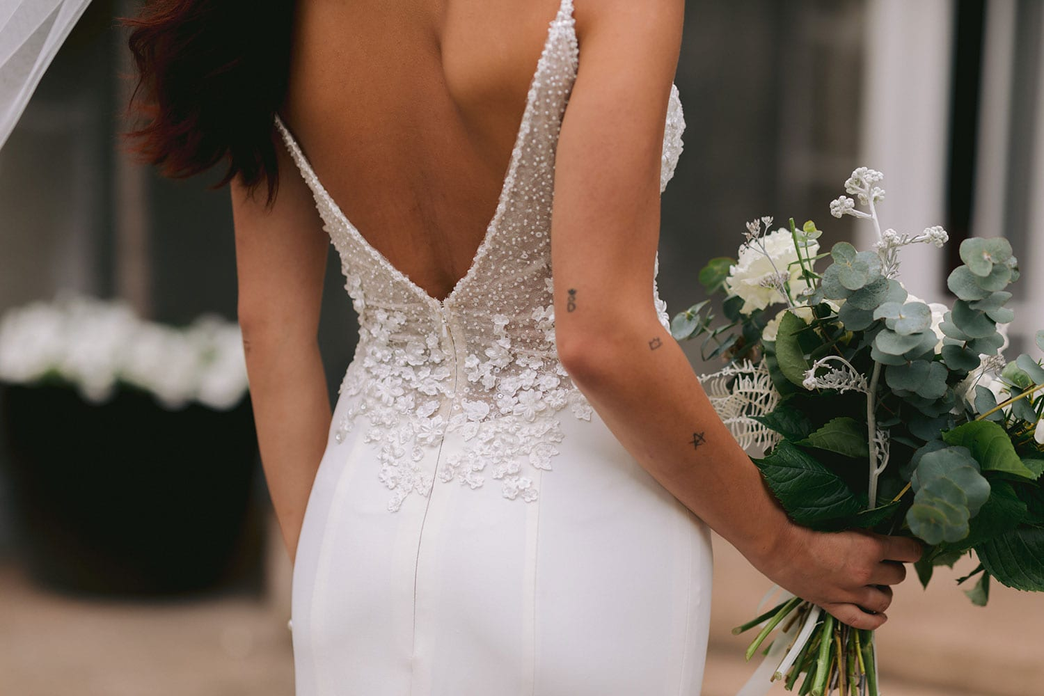 Azure Wedding Gown from Vinka Design - Elegantly tailored trouser combined with a beautiful lace blouse for the Modern Bride. The blouse features a high neck and low back, with in-built camisole, fitted sleeves, & pearl buttons. Model wearing gown , close up of V-back detail.