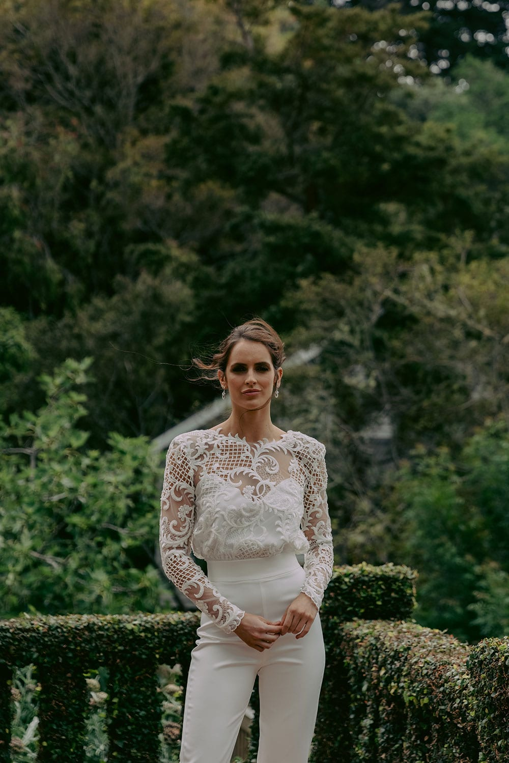 Aurora Wedding Trousers and Blouse from Vinka Design - Elegantly tailored trouser combined with a beautiful lace blouse for the Modern Bride. The blouse features a high neck and low back, with in-built camisole, fitted sleeves, & pearl buttons. Model wearing Trousers and Blouse in Clevedon Gardens near Auckland.
