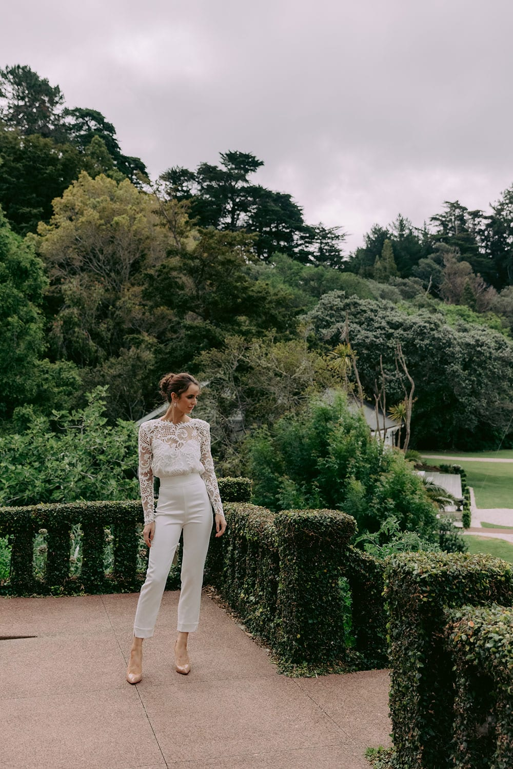 Aurora Wedding Trousers and Blouse from Vinka Design - Elegantly tailored trouser combined with a beautiful lace blouse for the Modern Bride. The blouse features a high neck and low back, with in-built camisole, fitted sleeves, & pearl buttons. Model wearing Trousers and Blouse in Clevedon Gardens, Auckland.