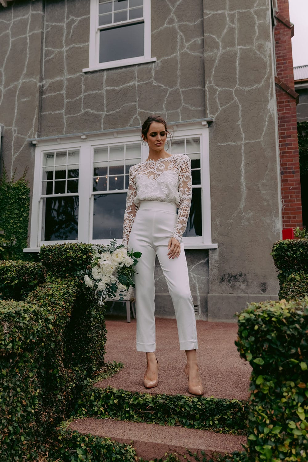 Aurora Wedding Trousers and Blouse from Vinka Design - Elegantly tailored trouser combined with a beautiful lace blouse for the Modern Bride. The blouse features a high neck and low back, with in-built camisole, fitted sleeves, & pearl buttons. Model wearing Trousers and Blouse outside Heritage building in Clevedon Gardens, Auckland.
