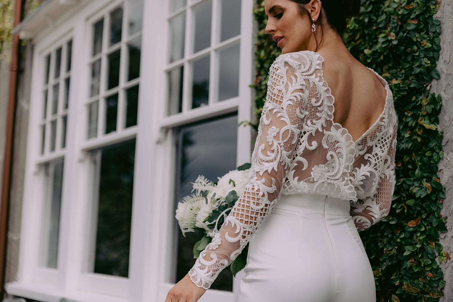 Aurora Wedding Trousers and Blouse from Vinka Design - Elegantly tailored trouser combined with a beautiful lace blouse for the Modern Bride. The blouse features a high neck and low back, with in-built camisole, fitted sleeves, & pearl buttons. Model wearing Trousers and Blouse showing low back detail of blouse outside Heritage building in Clevedon Gardens, Auckland.