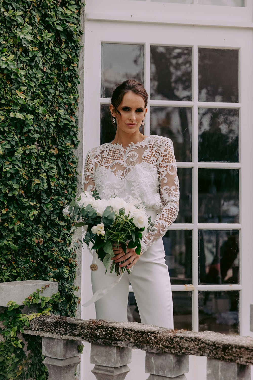 Aurora Wedding Trousers and Blouse from Vinka Design - Elegantly tailored trouser combined with a beautiful lace blouse for the Modern Bride. The blouse features a high neck and low back, with in-built camisole, fitted sleeves, & pearl buttons. Model wearing Trousers and Blouse showing front detail of blouse outside Heritage building in Clevedon Gardens, near Auckland.