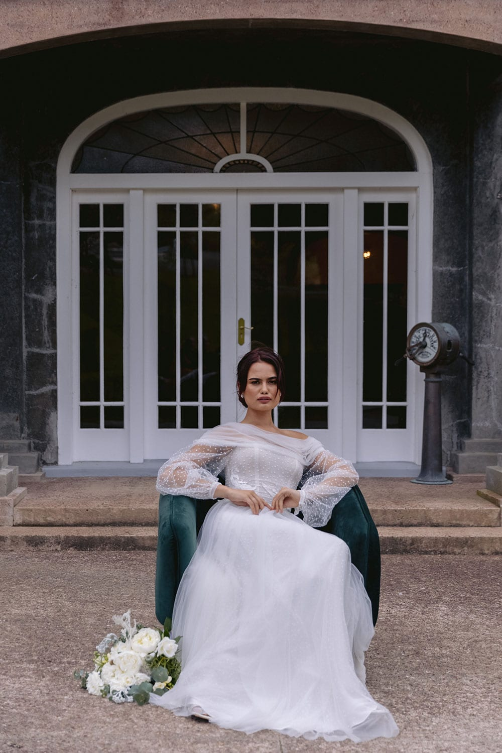 Aurora Wedding gown from Vinka Design - This dreamy wedding gown has soft hailstone tulle draped around the decolletage and over the shoulders, where it falls into a V-shaped back. Delicate puff sleeves with elegant pearl button cuffs. Structured bodice and soft skirt with train. Model wearing gown outside heritage building sitting in chair.