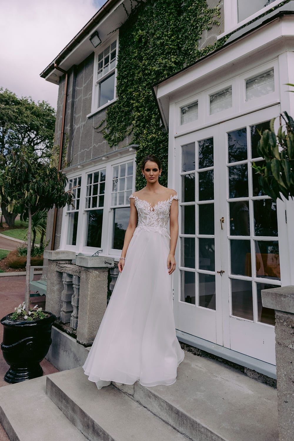 Ariana Wedding gown from Vinka Design - This gorgeous gown features delicate leaf lace hand-appliqued throughout the semi-sheer, structured bodice and up over the shoulder and skirt made of dreamy satin organza layers. Model wearing gown on steps outside country home