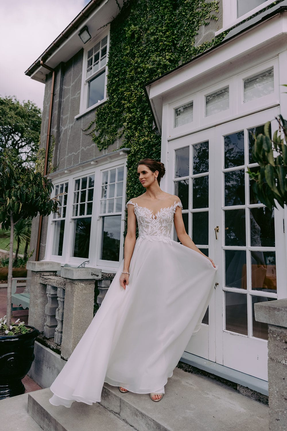 Ariana Wedding gown from Vinka Design - This gorgeous gown features delicate leaf lace hand-appliqued throughout the semi-sheer, structured bodice and up over the shoulder and skirt made of dreamy satin organza layers. Model wearing gown on steps outside country home holding satin skirt out.