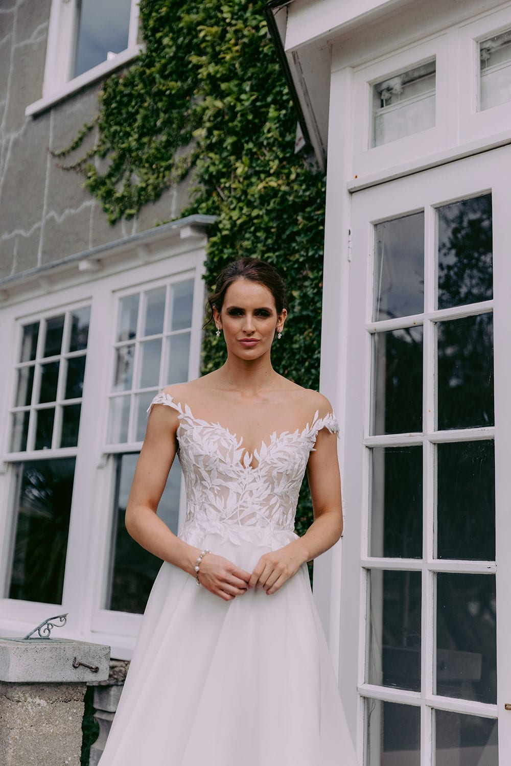 Ariana Wedding gown from Vinka Design - This gorgeous gown features delicate leaf lace hand-appliqued throughout the semi-sheer, structured bodice and up over the shoulder and skirt made of dreamy satin organza layers. Model wearing gown on steps outside country home close up of lace detail on bodice..