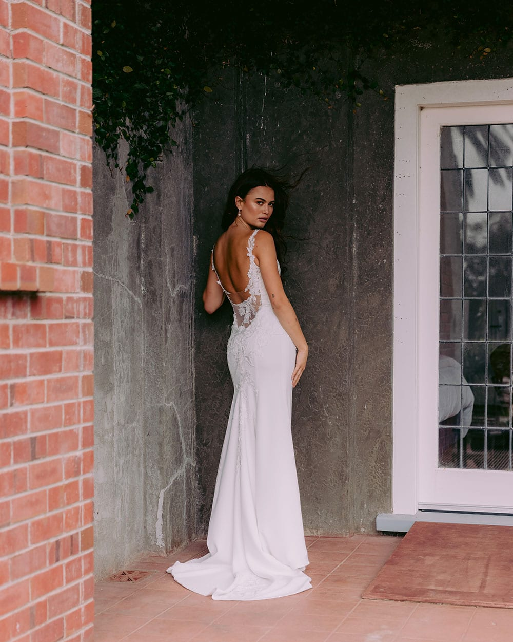 Ana Wedding gown from Vinka Design - This beautiful gown is graced by hand-appliqued delicate floral leaf lace, subtly worked into the front of the bodice and more prominently on the back. A fit-and-flare cut shapes the figure. Model wearing gown showing low back and lace detail.