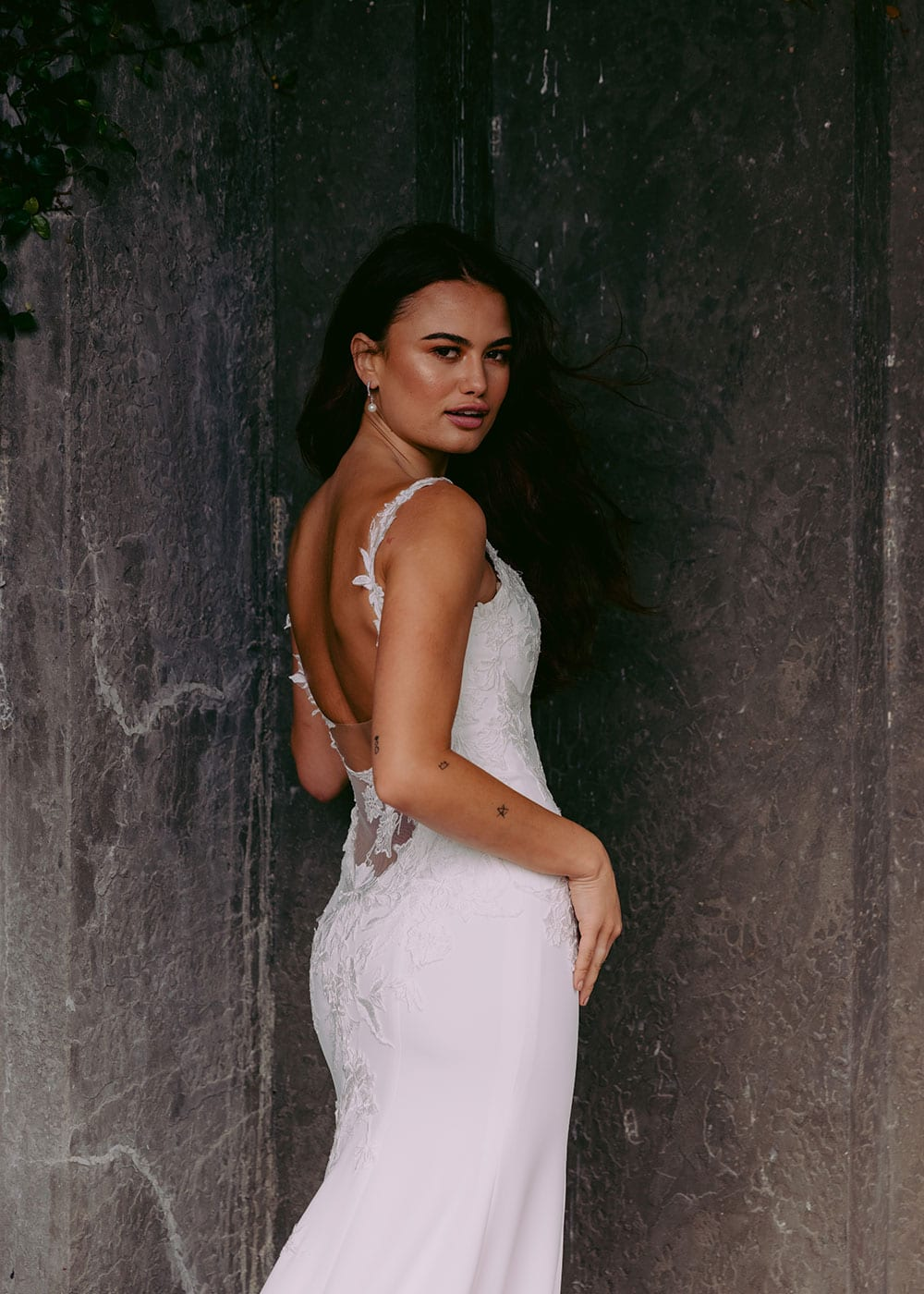 Ana Wedding gown from Vinka Design - This beautiful gown is graced by hand-appliqued delicate floral leaf lace, subtly worked into the front of the bodice and more prominently on the back. A fit-and-flare cut shapes the figure. Model wearing gown showing back lace detail and scultped fit..