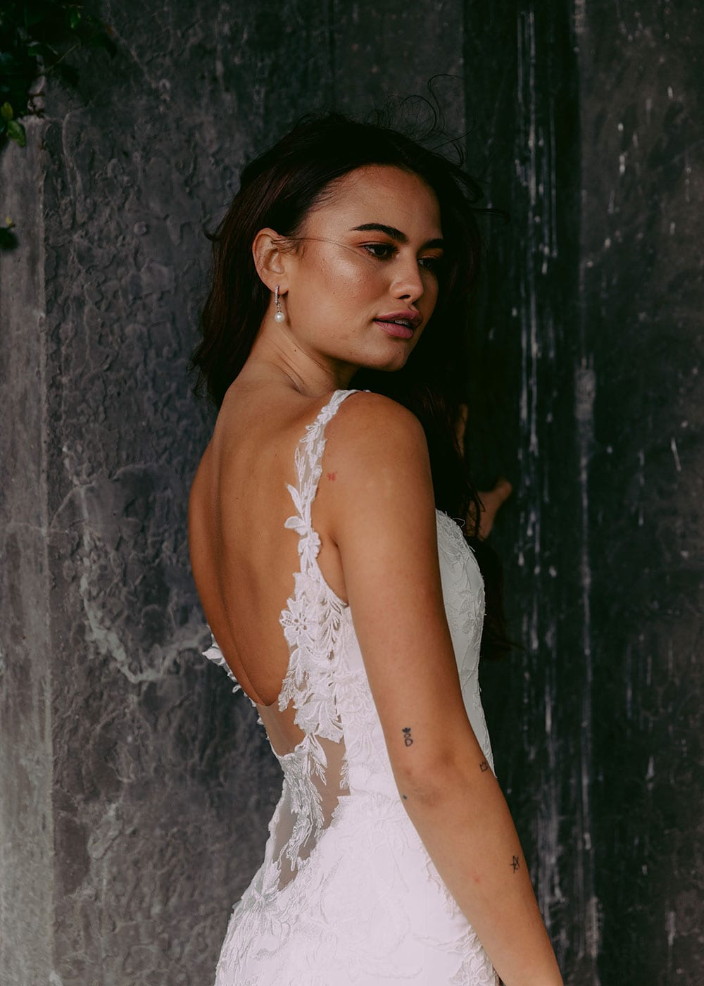 Ana Wedding gown from Vinka Design - This beautiful gown is graced by hand-appliqued delicate floral leaf lace, subtly worked into the front of the bodice and more prominently on the back. A fit-and-flare cut shapes the figure. Model wearing gown highlighting side and lace detail.
