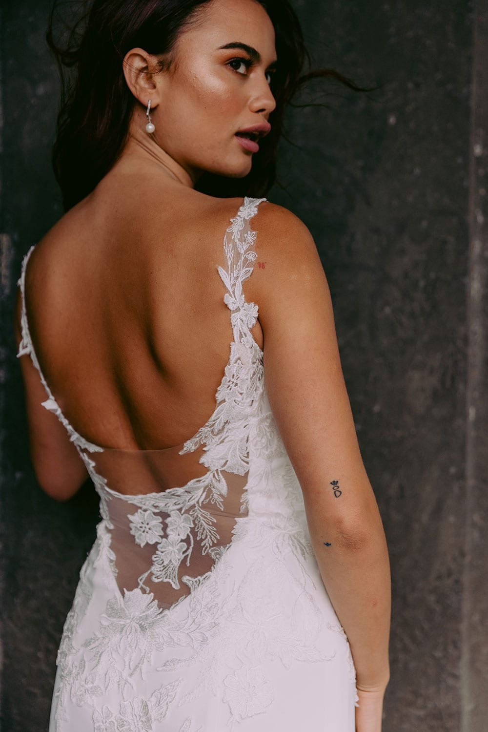 Ana Wedding gown from Vinka Design - This beautiful gown is graced by hand-appliqued delicate floral leaf lace, subtly worked into the front of the bodice and more prominently on the back. A fit-and-flare cut shapes the figure. Model wearing gown highlighting low back of dress with lace detail.