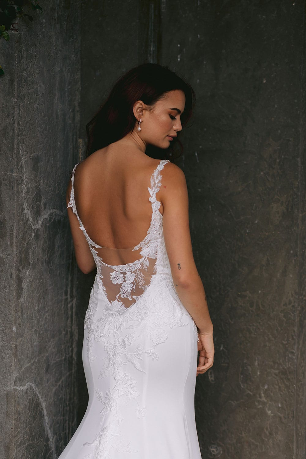 Ana Wedding gown from Vinka Design - This beautiful gown is graced by hand-appliqued delicate floral leaf lace, subtly worked into the front of the bodice and more prominently on the back. A fit-and-flare cut shapes the figure. Model wearing gown highlighting back of dress lace detail with bodice.