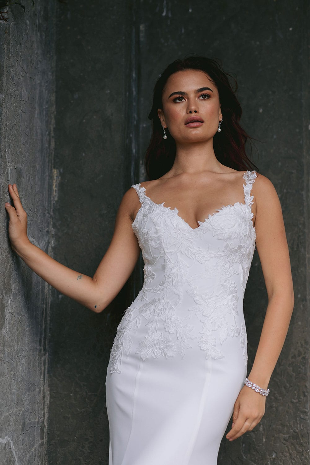 Ana Wedding gown from Vinka Design - This beautiful gown is graced by hand-appliqued delicate floral leaf lace, subtly worked into the front of the bodice and more prominently on the back. A fit-and-flare cut shapes the figure. Model wearing gown highlighting fit and flare bodice lace detail.