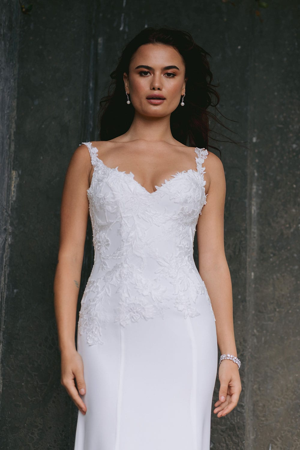 Ana Wedding gown from Vinka Design - This beautiful gown is graced by hand-appliqued delicate floral leaf lace, subtly worked into the front of the bodice and more prominently on the back. A fit-and-flare cut shapes the figure. Model wearing gown highlighting fit and flare shape.
