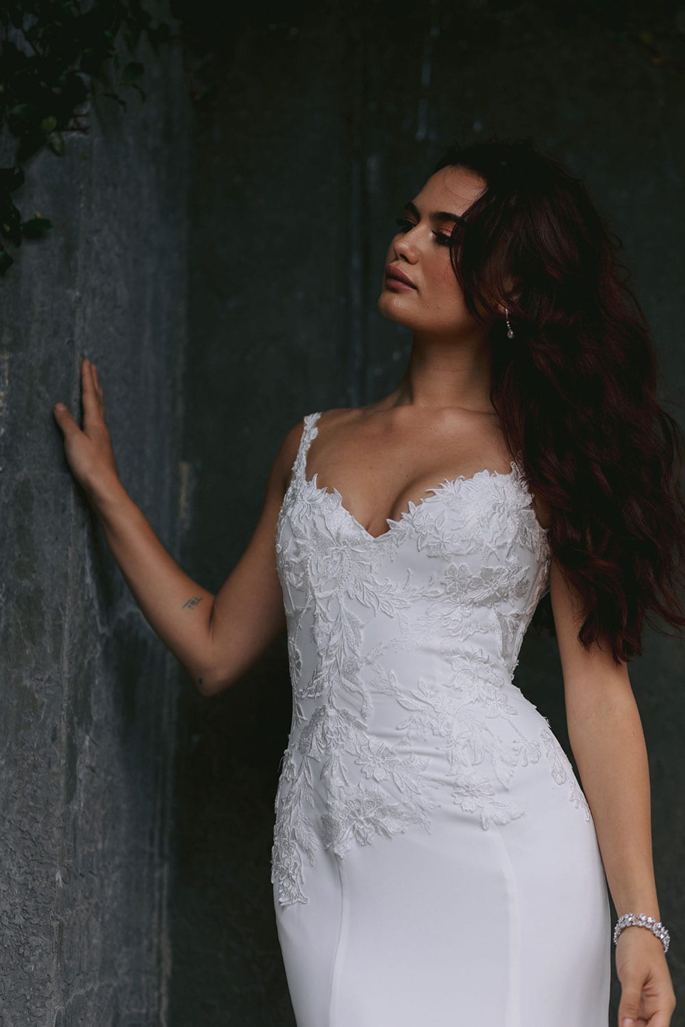 Ana Wedding gown from Vinka Design - This beautiful gown is graced by hand-appliqued delicate floral leaf lace, subtly worked into the front of the bodice and more prominently on the back. A fit-and-flare cut shapes the figure. Model wearing gown highlighting bodice shape.