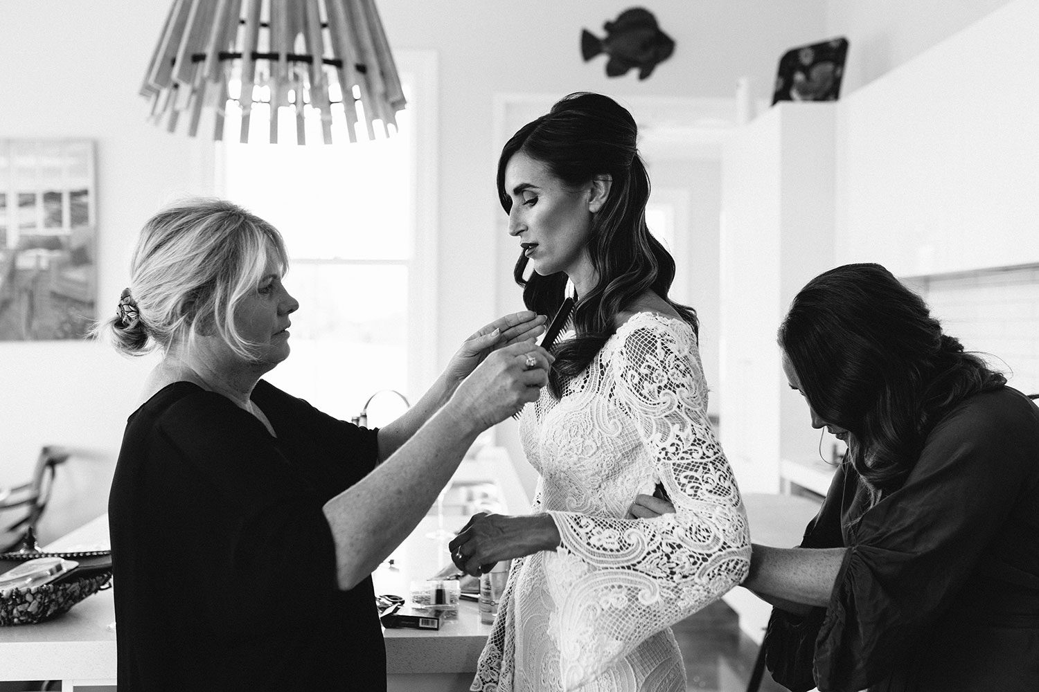 Bride wearing Sabine wedding gown by Auckland wedding dress maker Vinka Design, with French crochet lace detail and long sleeves - black and white getting ready