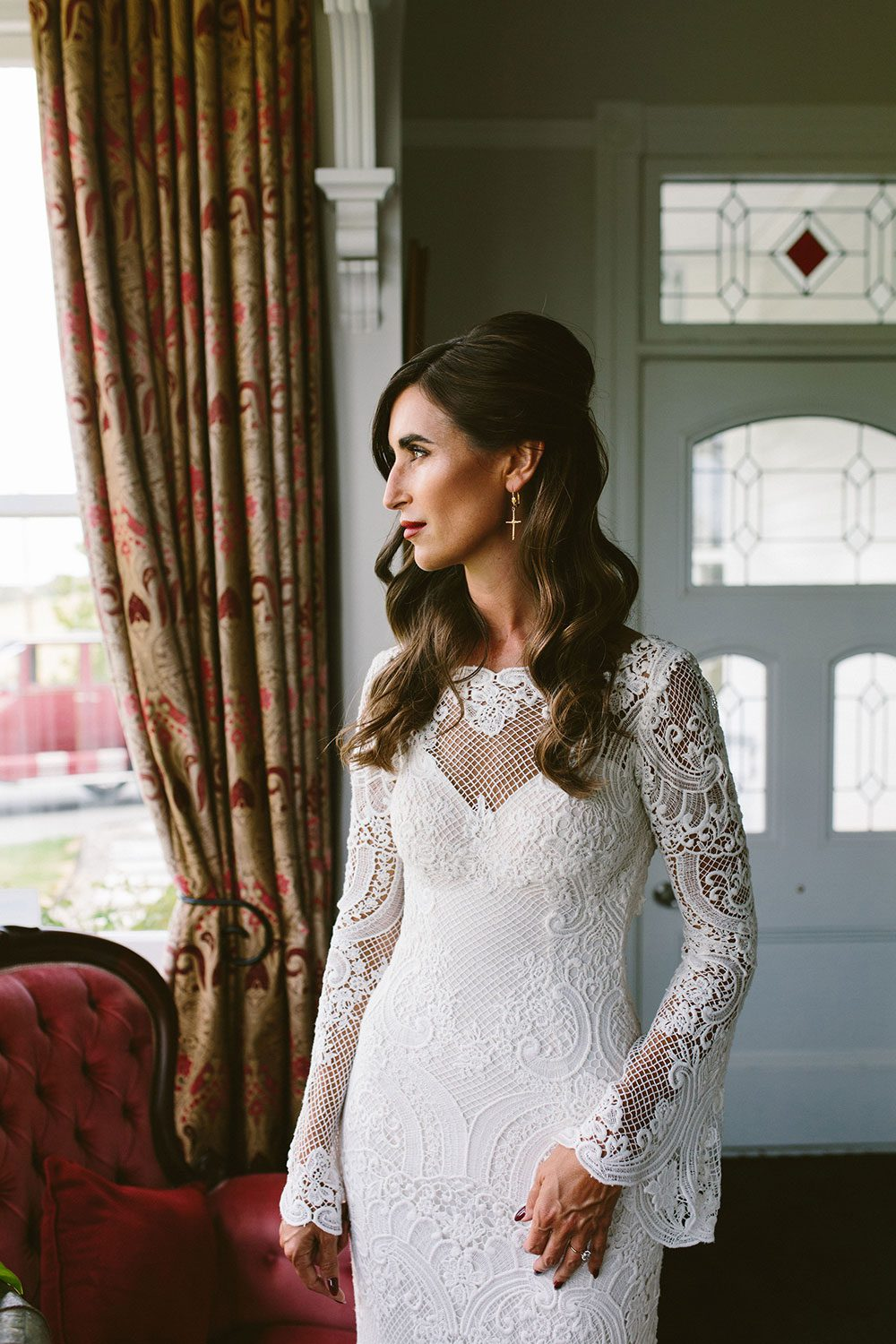Bride wearing Sabine wedding gown by Auckland wedding dress maker Vinka Design, with French crochet lace detail and long sleeves - at window