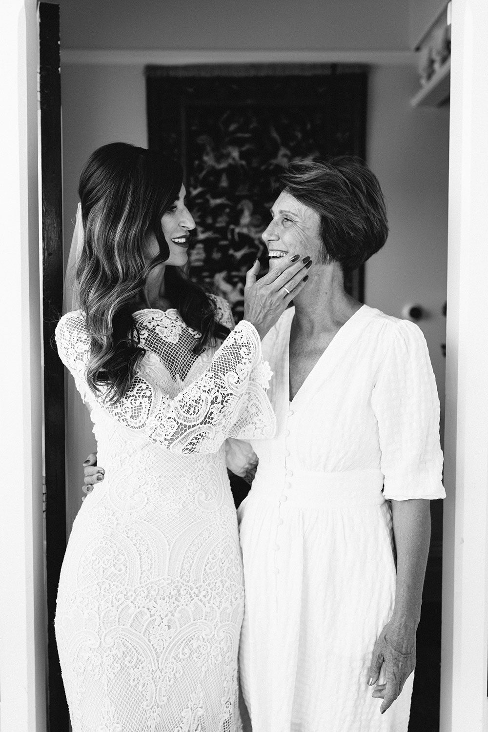 Bride wearing Sabine wedding gown by Auckland wedding dress maker Vinka Design, with French crochet lace detail and long sleeves - black and white with mother