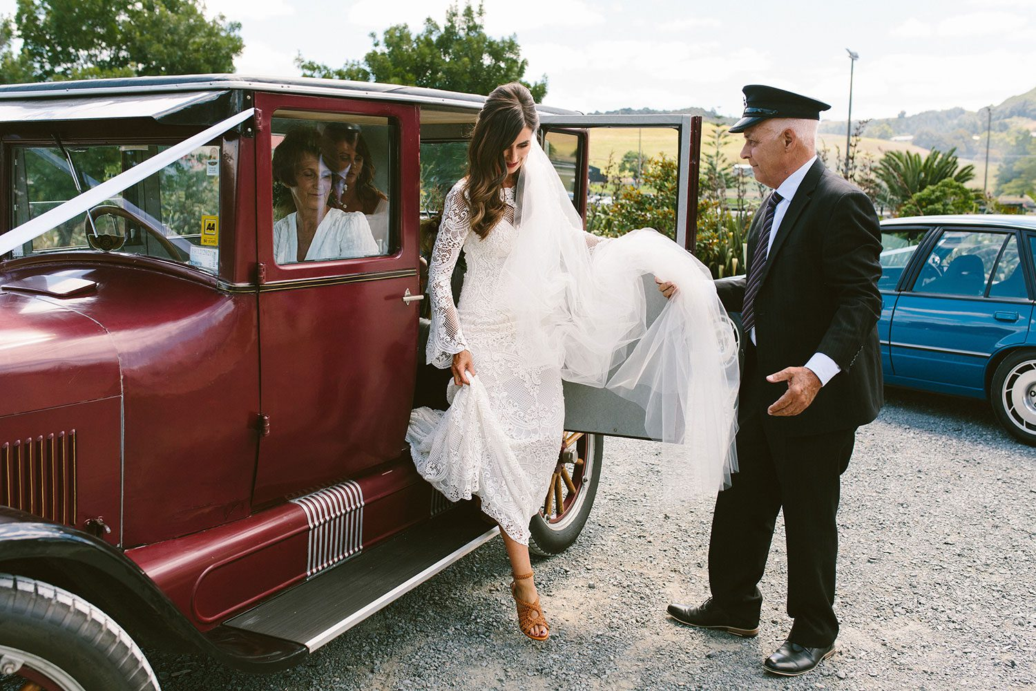 Bride wearing Sabine wedding gown by Auckland wedding dress maker Vinka Design, with French crochet lace detail and long sleeves - stepping out of vintage car