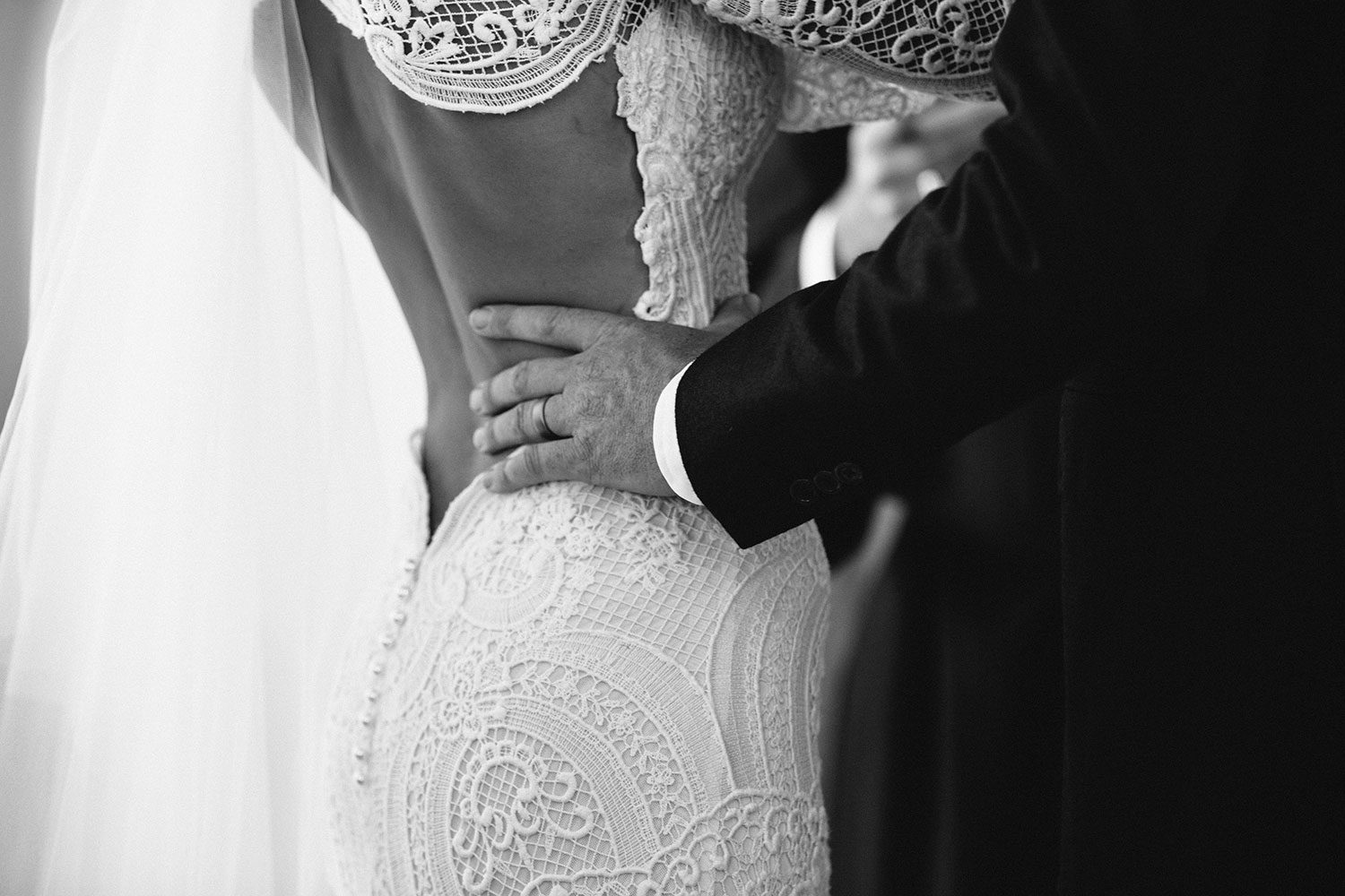 Bride wearing Sabine wedding gown by Auckland wedding dress maker Vinka Design, with French crochet lace detail and long sleeves - close up of back of dress
