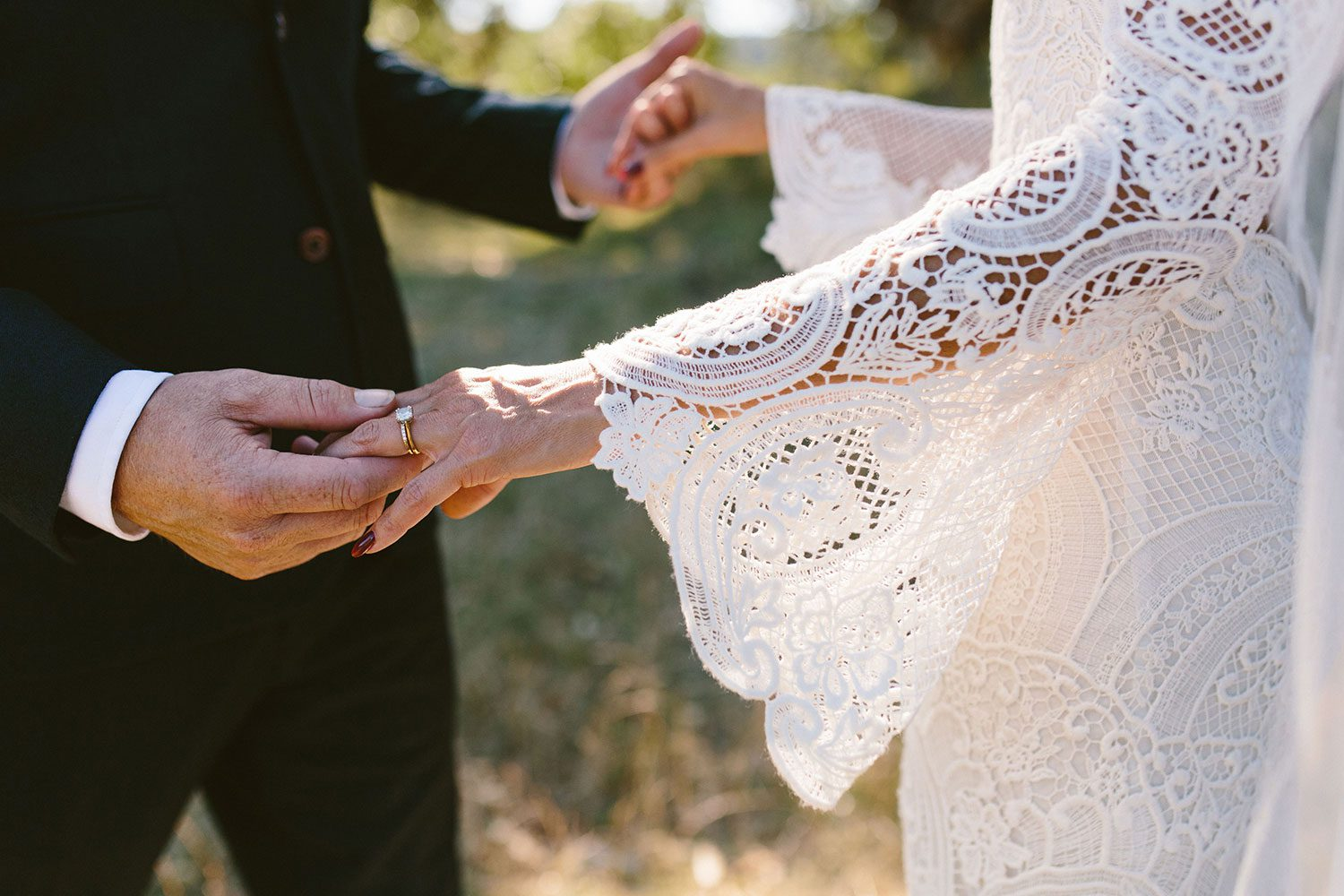Bride wearing Sabine wedding gown by Auckland wedding dress maker Vinka Design, with French crochet lace detail and long sleeves - close up of sleeves