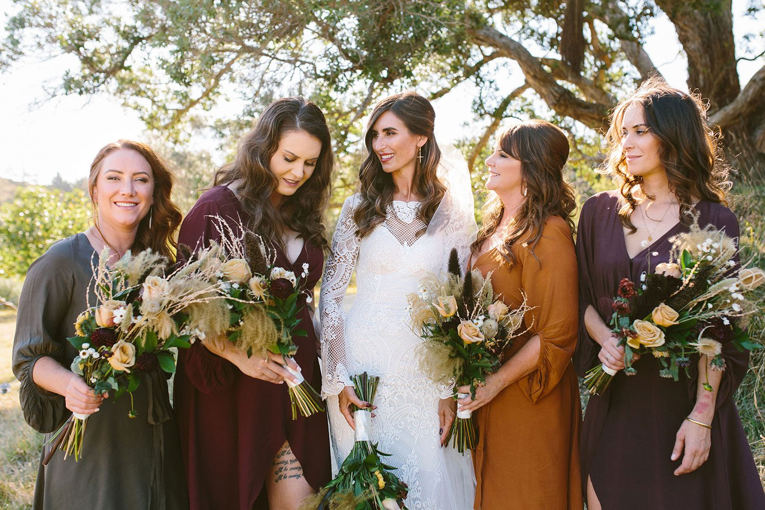 Bride wearing Sabine wedding gown by Auckland wedding dress maker Vinka Design, with French crochet lace detail and long sleeves - with bridesmaids