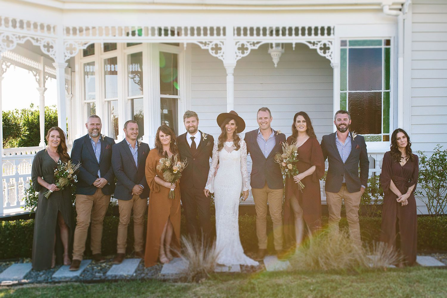 Bride wearing Sabine wedding gown by Auckland wedding dress maker Vinka Design, with French crochet lace detail and long sleeves - with bridal party