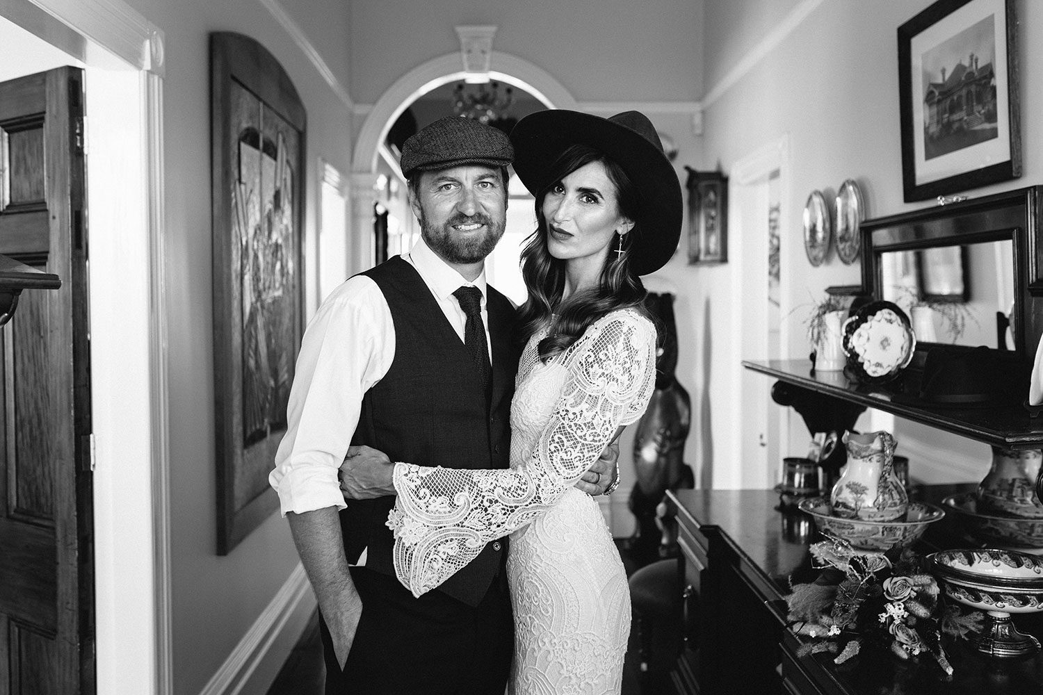 Bride wearing Sabine wedding gown by Auckland wedding dress maker Vinka Design, with French crochet lace detail and long sleeves - black and white in hallway