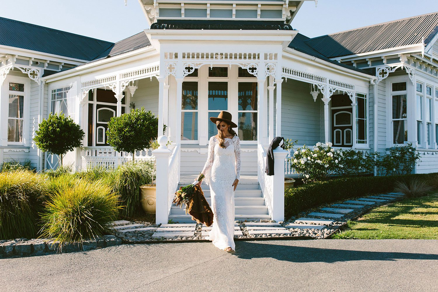 Bride wearing Sabine wedding gown by Auckland wedding dress maker Vinka Design, with French crochet lace detail and long sleeves - in front of house