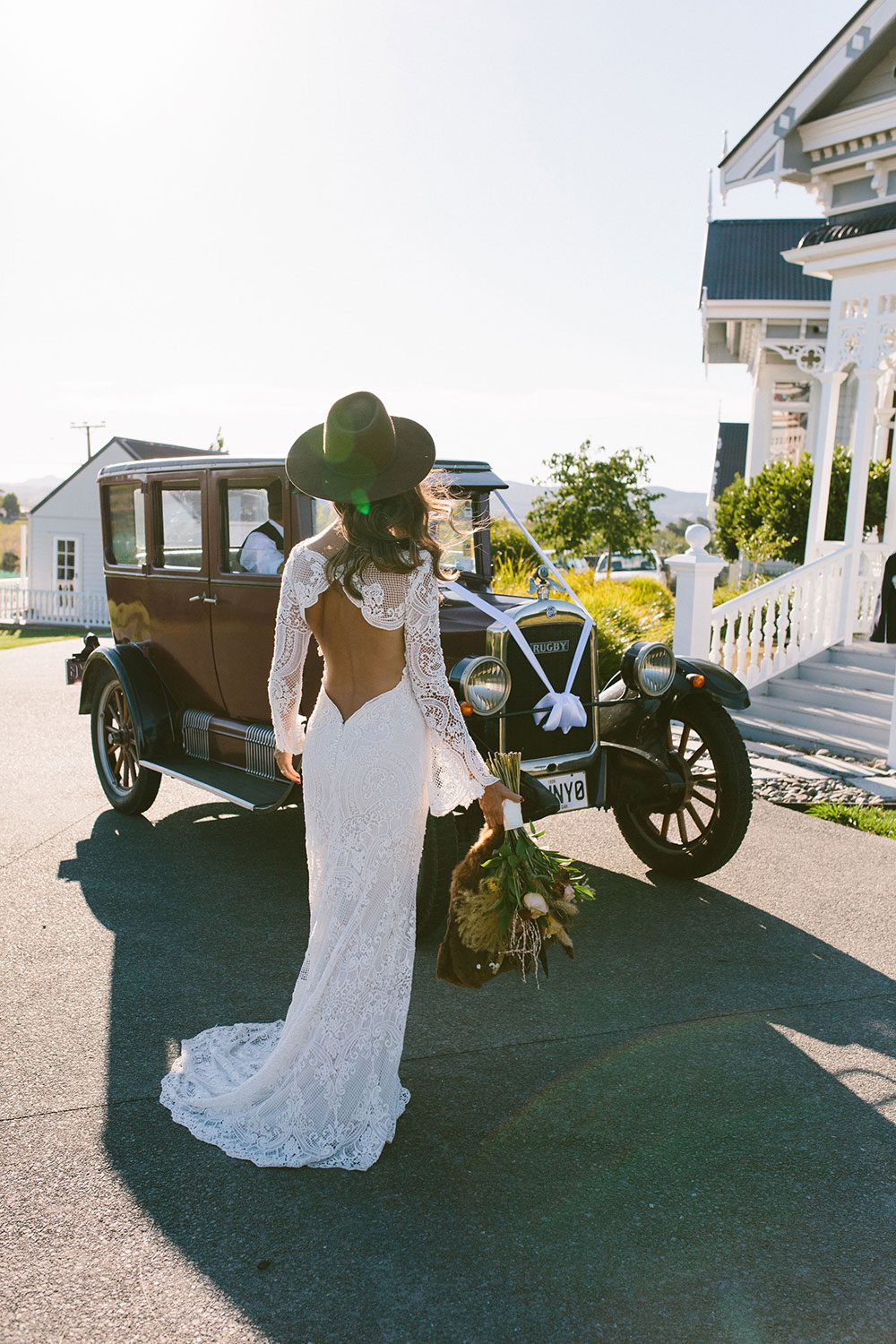 Bride wearing Sabine wedding gown by Auckland wedding dress maker Vinka Design, with French crochet lace detail and long sleeves - in front of vintage car