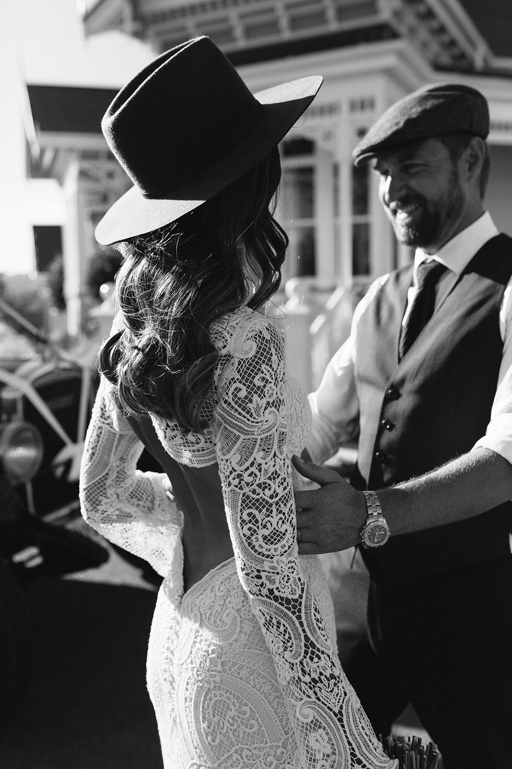 Bride wearing Sabine wedding gown by Auckland wedding dress maker Vinka Design, with French crochet lace detail and long sleeves - black and white image
