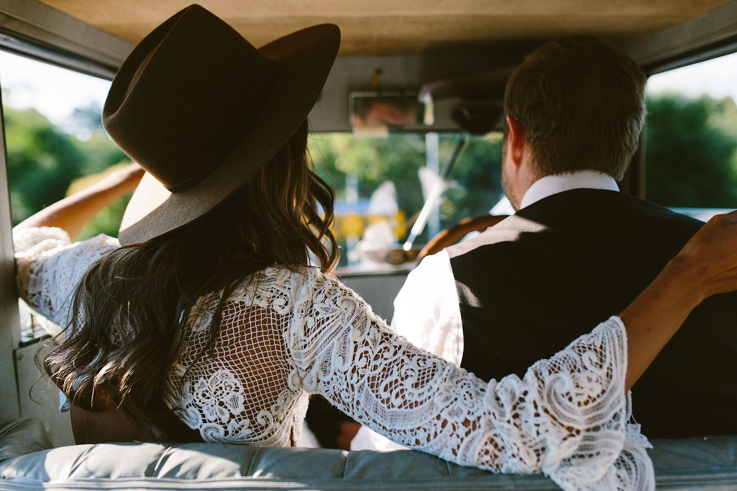 Bride wearing Sabine wedding gown by Auckland wedding dress maker Vinka Design, with French crochet lace detail and long sleeves - in vintage car with groom