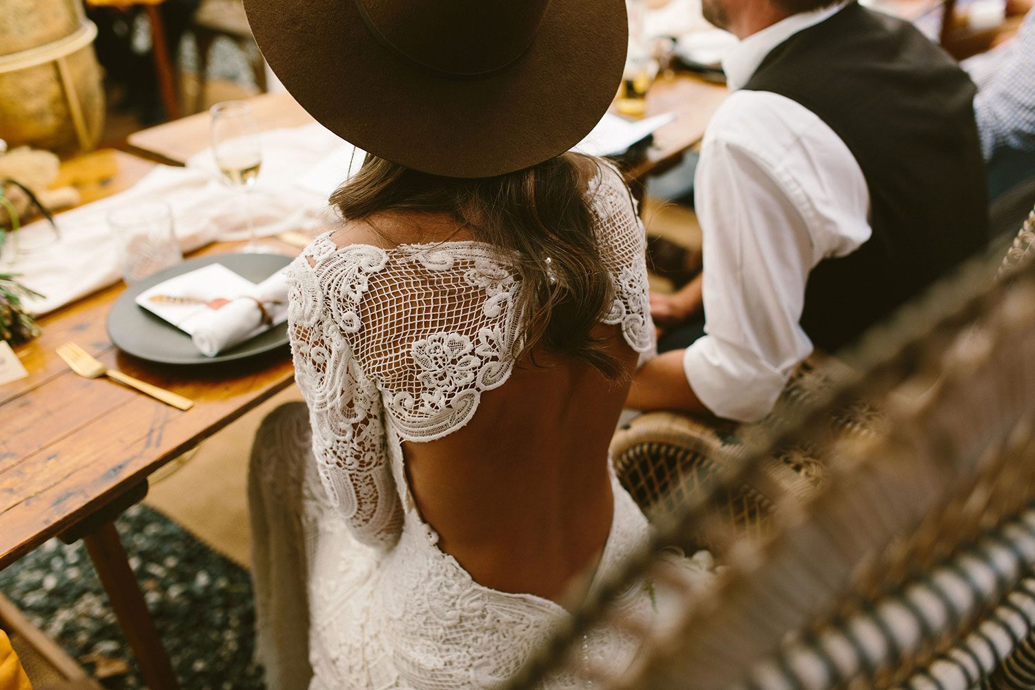 Bride wearing Sabine wedding gown by Auckland wedding dress maker Vinka Design, with French crochet lace detail and long sleeves - at head table