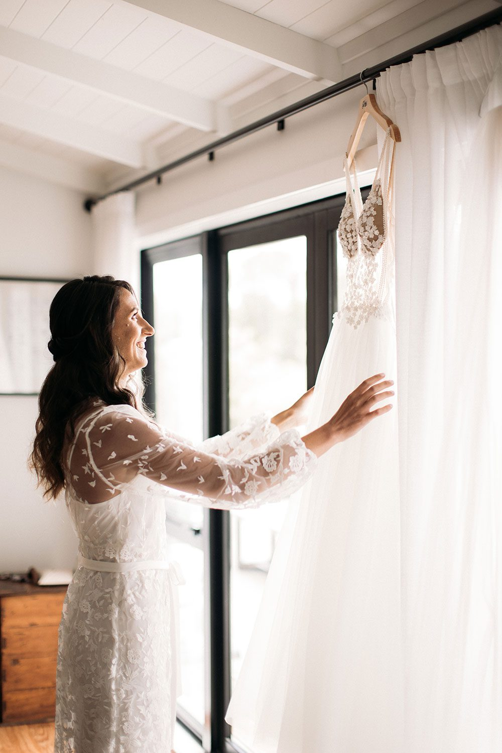 Vinka bridal boutique Isabelle tulle gown with sheer v neck bodice and beaded lace - with bride at window