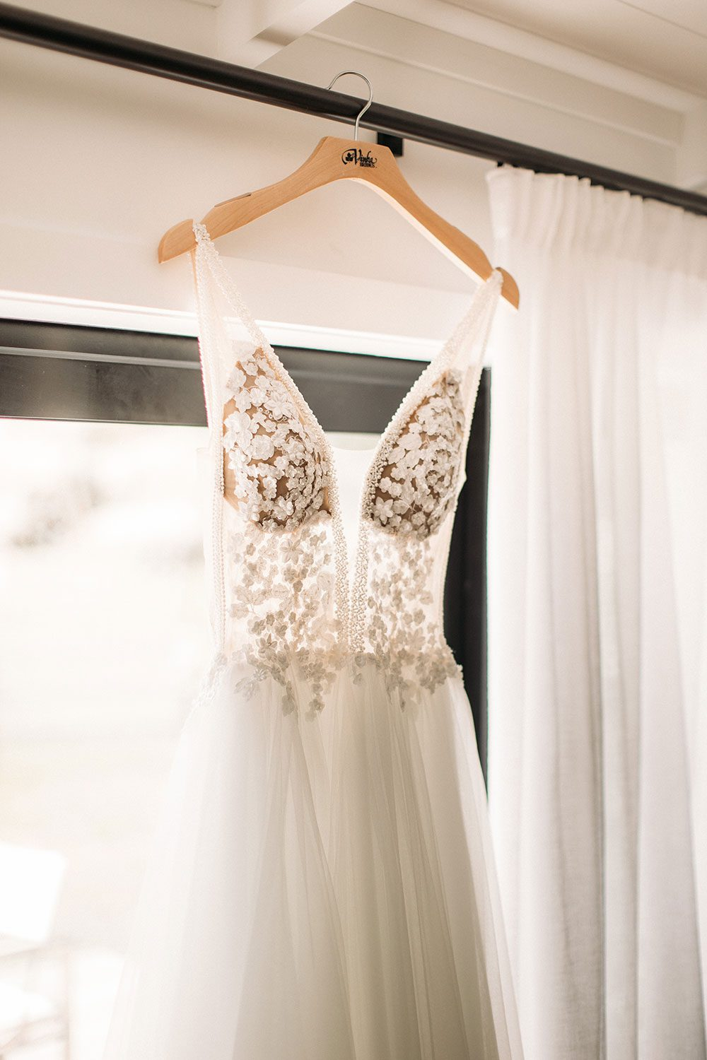 Vinka bridal boutique Isabelle tulle gown with sheer v neck bodice and beaded lace - hanging in window