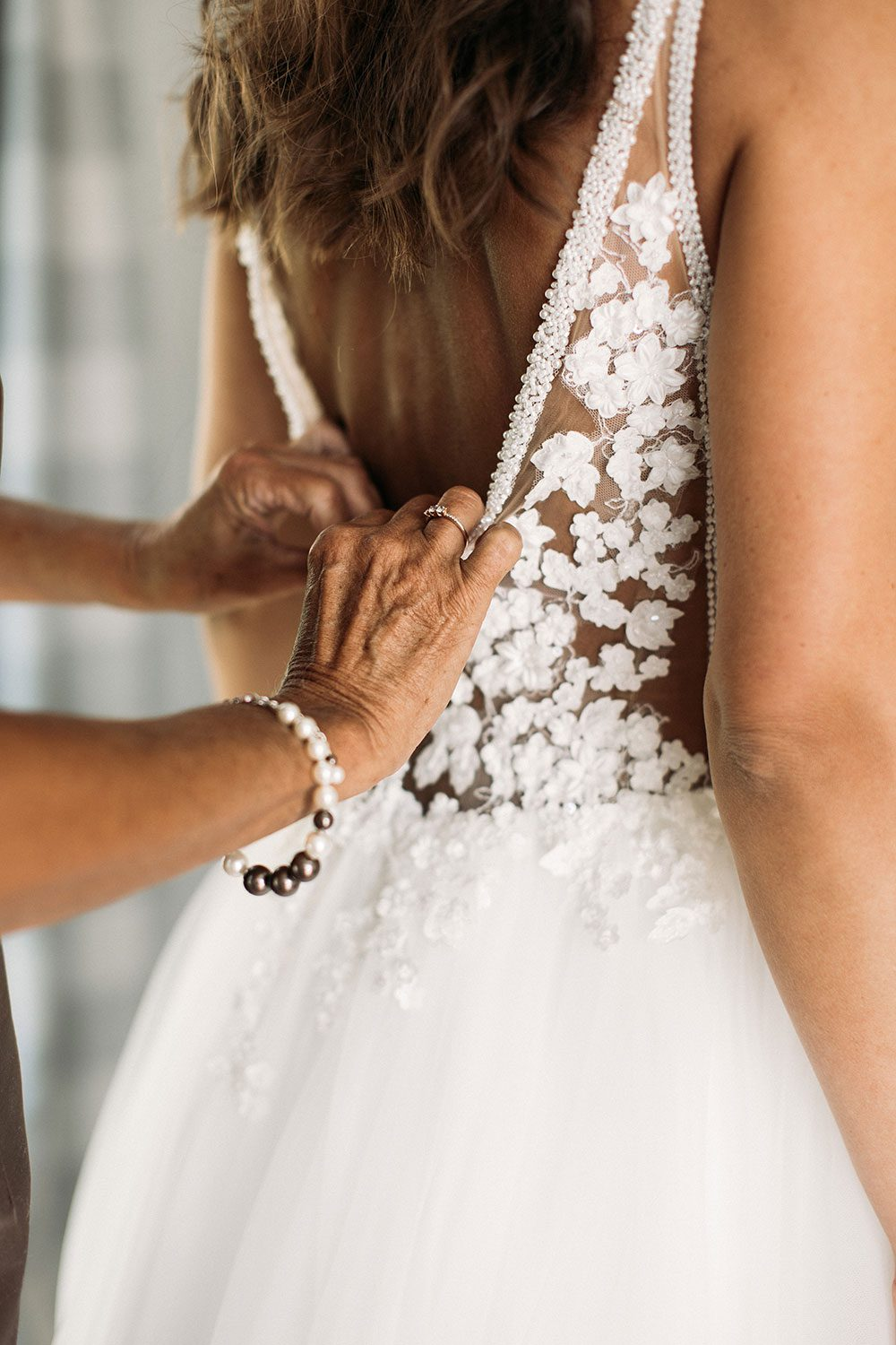 Bride wearing Vinka bridal boutique Isabelle tulle gown with sheer v neck bodice and beaded lace - back of dress