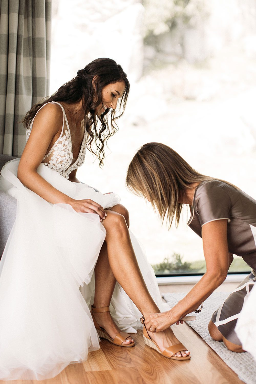 Bride wearing Vinka bridal boutique Isabelle tulle gown with sheer v neck bodice and beaded lace - fitting shoes
