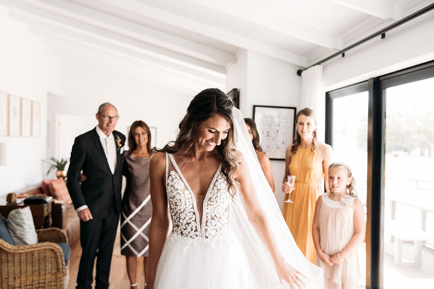 Bride wearing Vinka bridal boutique Isabelle tulle gown with sheer v neck bodice and beaded lace - with family