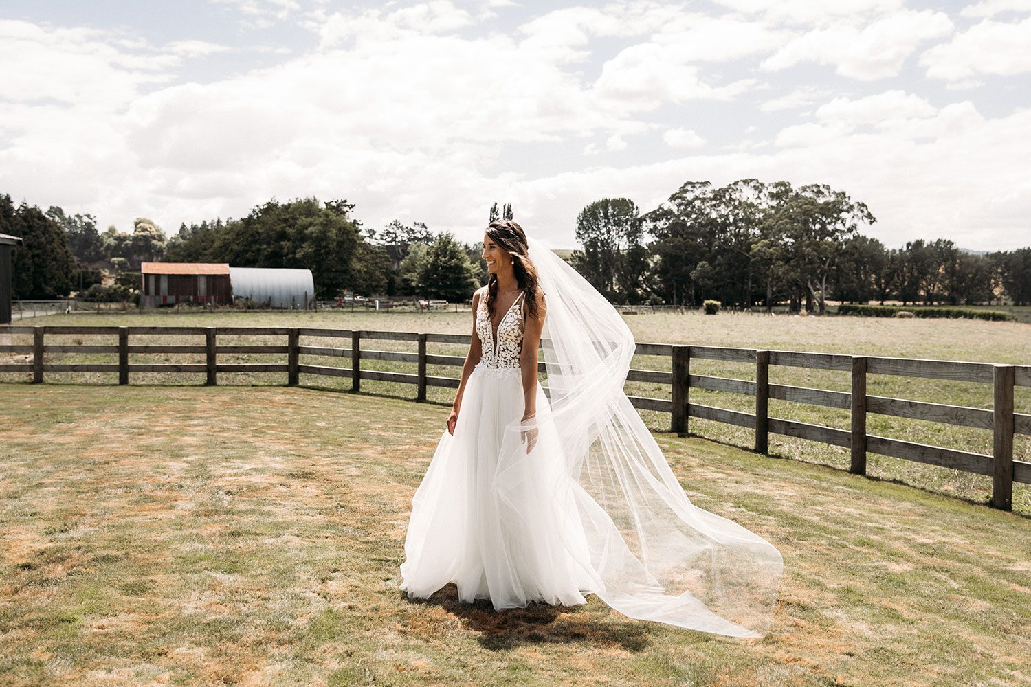 Bride wearing Vinka bridal boutique Isabelle tulle gown with sheer v neck bodice and beaded lace - in field