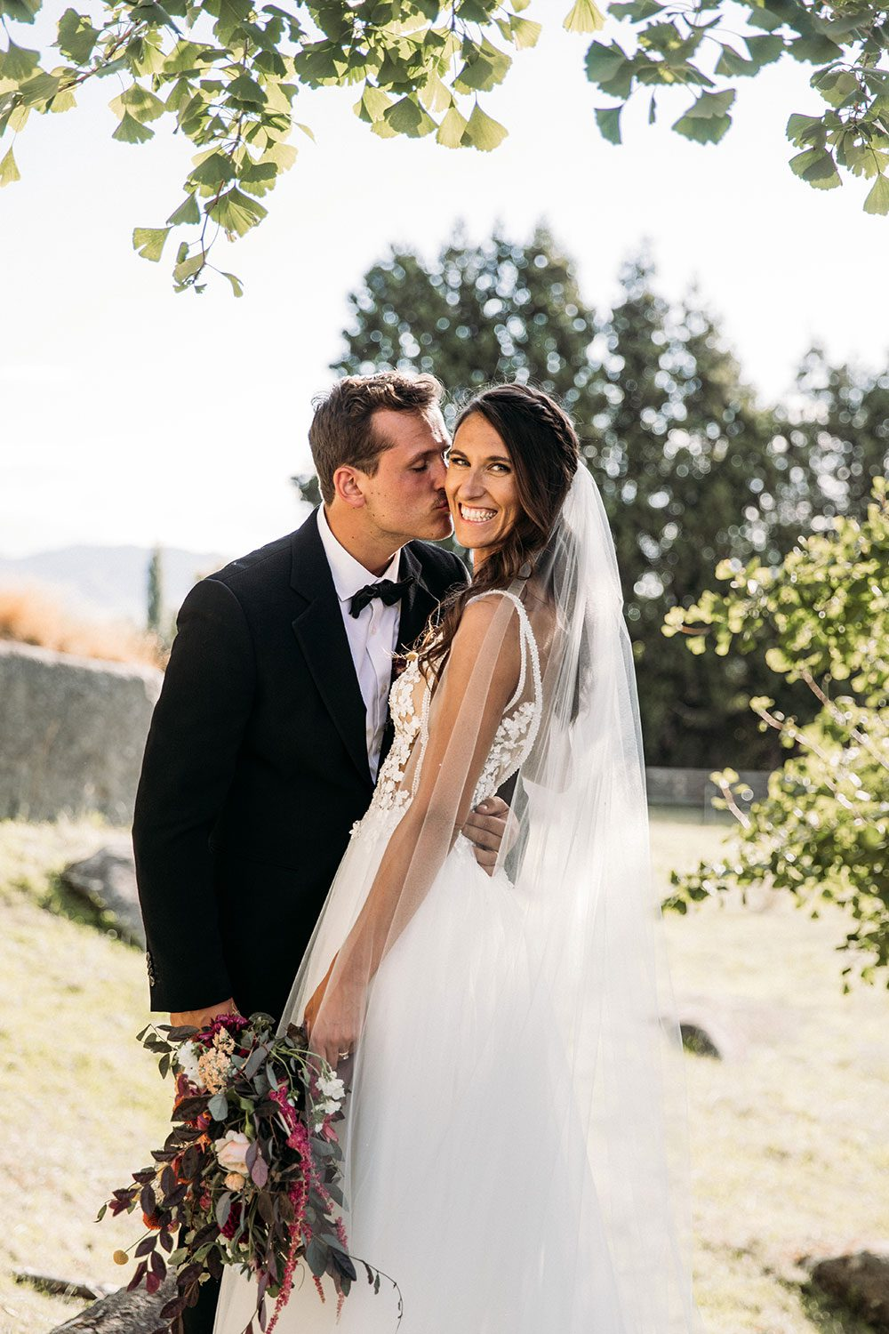 Bride wearing Vinka bridal boutique Isabelle tulle gown with sheer v neck bodice and beaded lace - with groom embrace under leaves