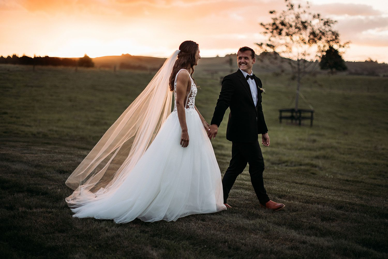Bride wearing Vinka bridal boutique Isabelle tulle gown with sheer v neck bodice and beaded lace - with groom in field