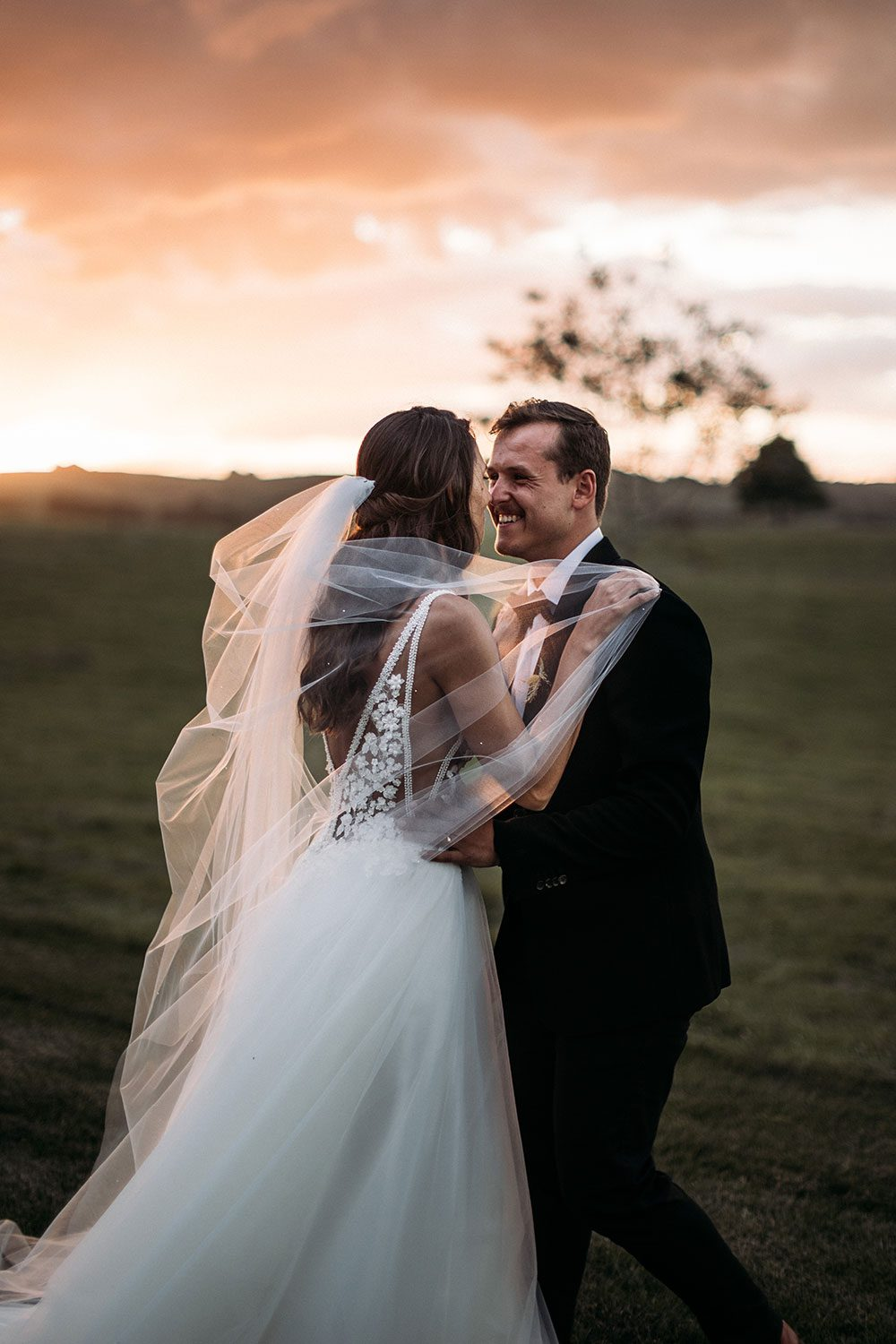 Bride wearing Vinka bridal boutique Isabelle tulle gown with sheer v neck bodice and beaded lace - embrace sunset