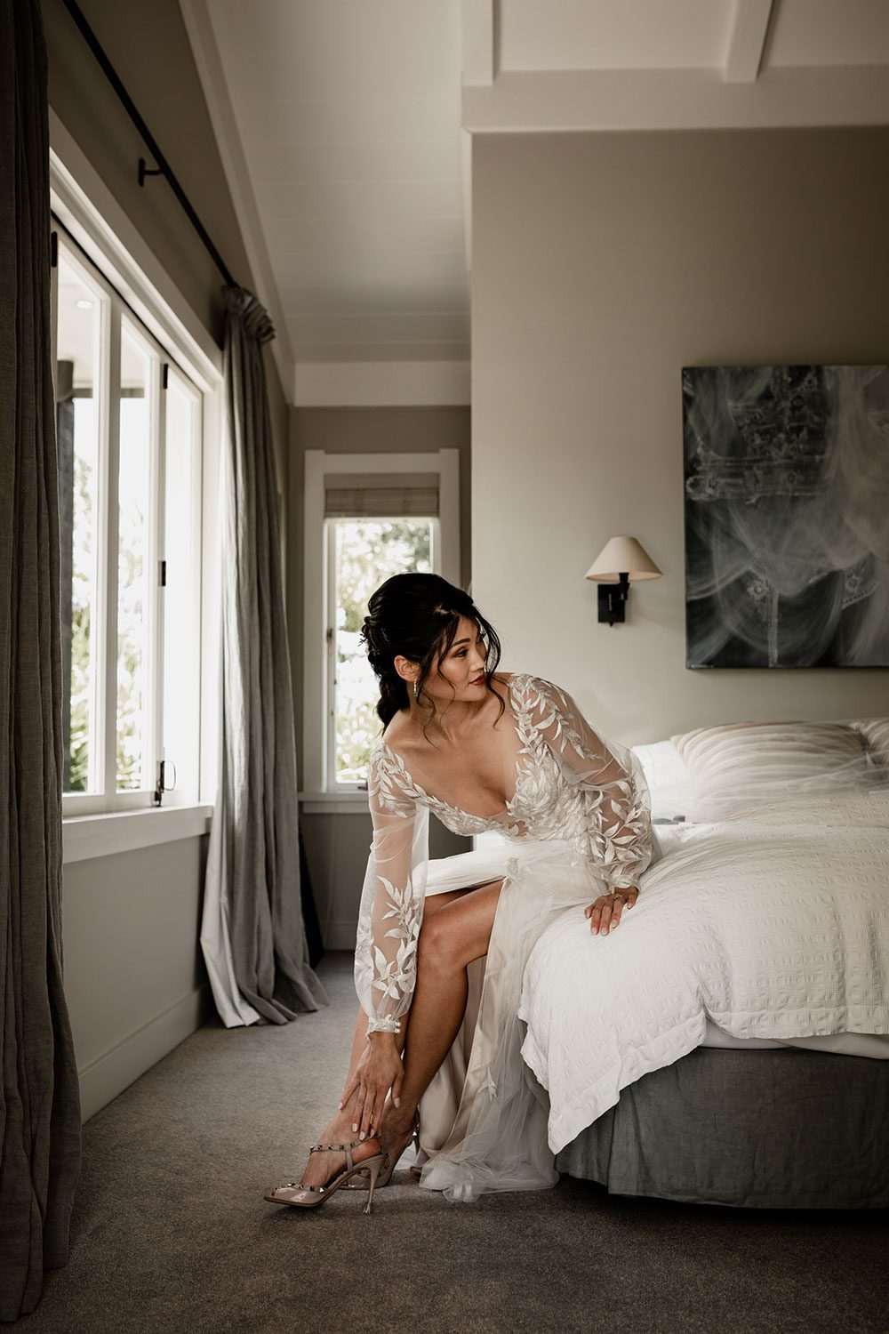 Bride wearing bespoke designer wedding dress by Vinka Bridal Boutique NZ, adorned with delicate applique lace and puffed sleeves - on bed