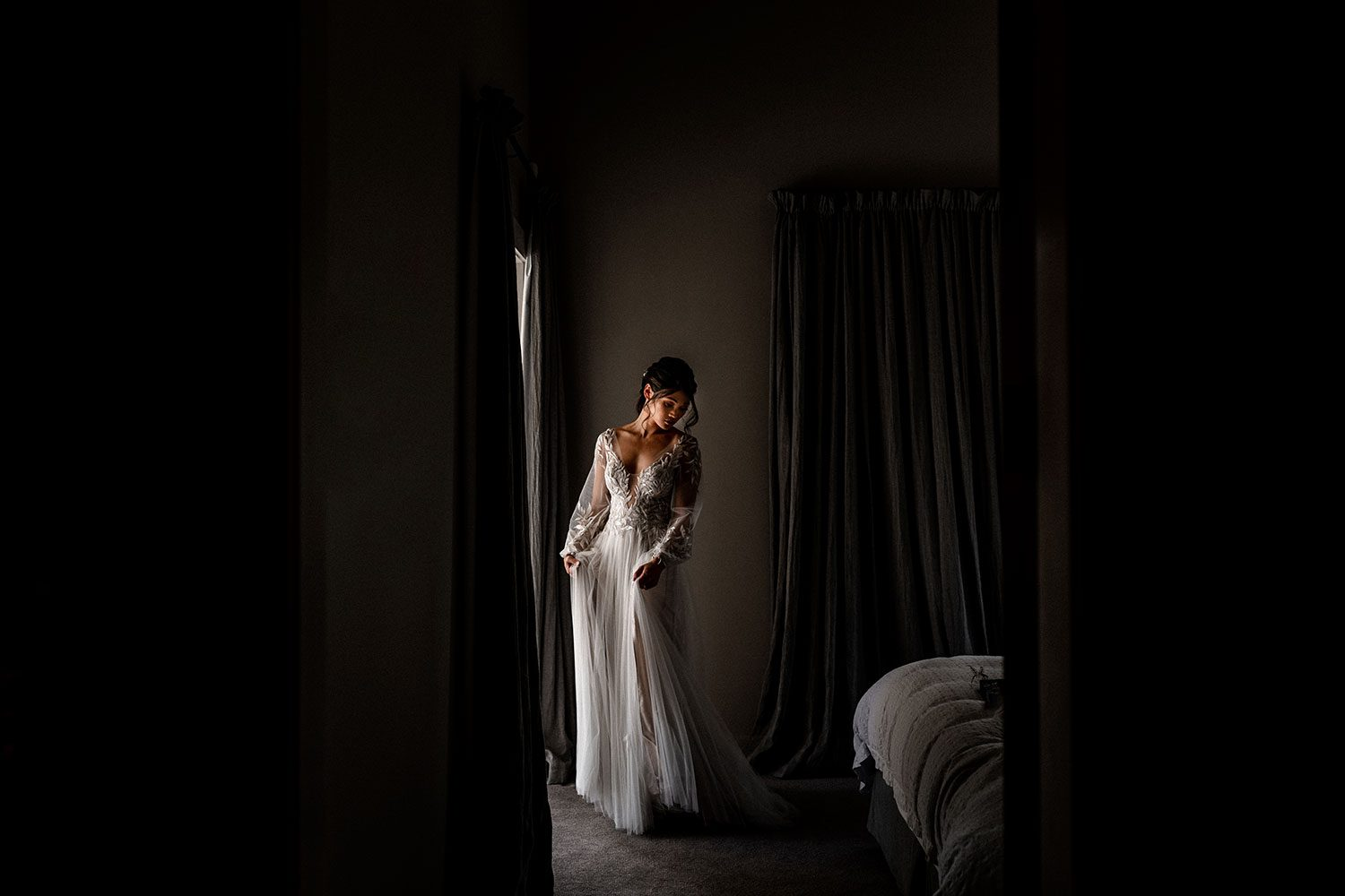Bride wearing bespoke designer wedding dress by Vinka Bridal Boutique NZ, adorned with delicate applique lace and puffed sleeves - in bedroom