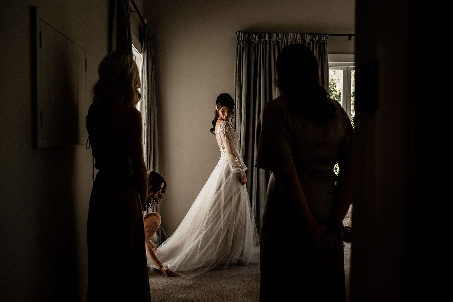 Bride wearing bespoke designer wedding dress by Vinka Bridal Boutique NZ, adorned with delicate applique lace and puffed sleeves - standing near window