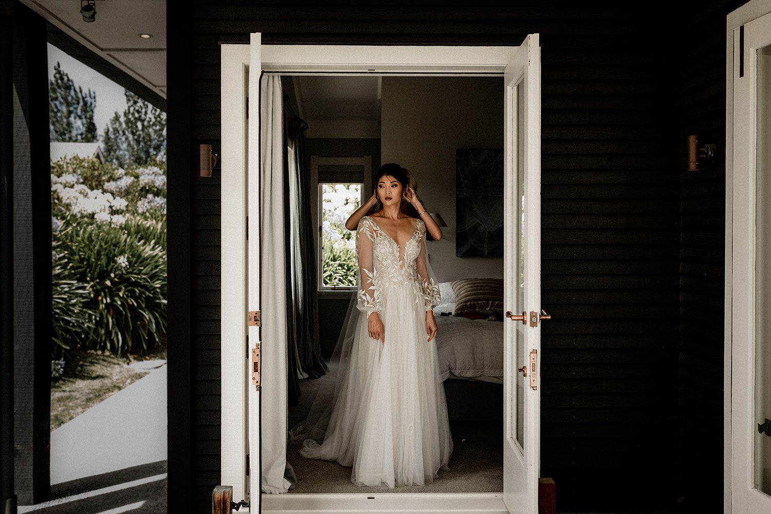 Bride wearing bespoke designer wedding dress by Vinka Bridal Boutique NZ, adorned with delicate applique lace and puffed sleeves - in doorway