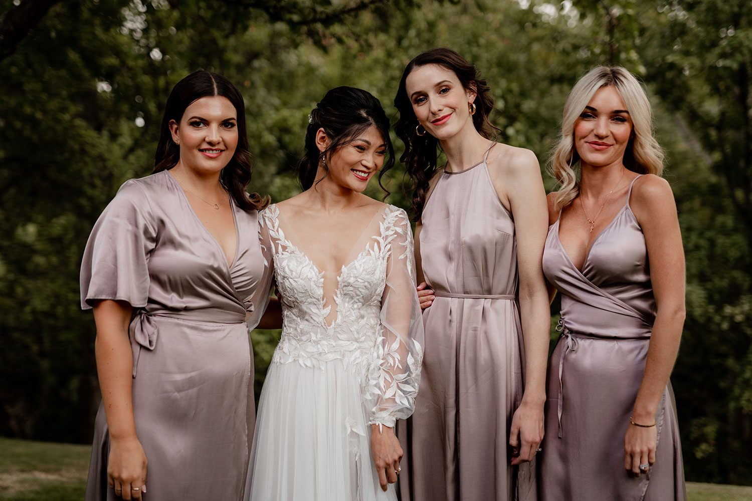 Bride wearing bespoke designer wedding dress by Vinka Bridal Boutique NZ, adorned with delicate applique lace and puffed sleeves - with bridesmaids