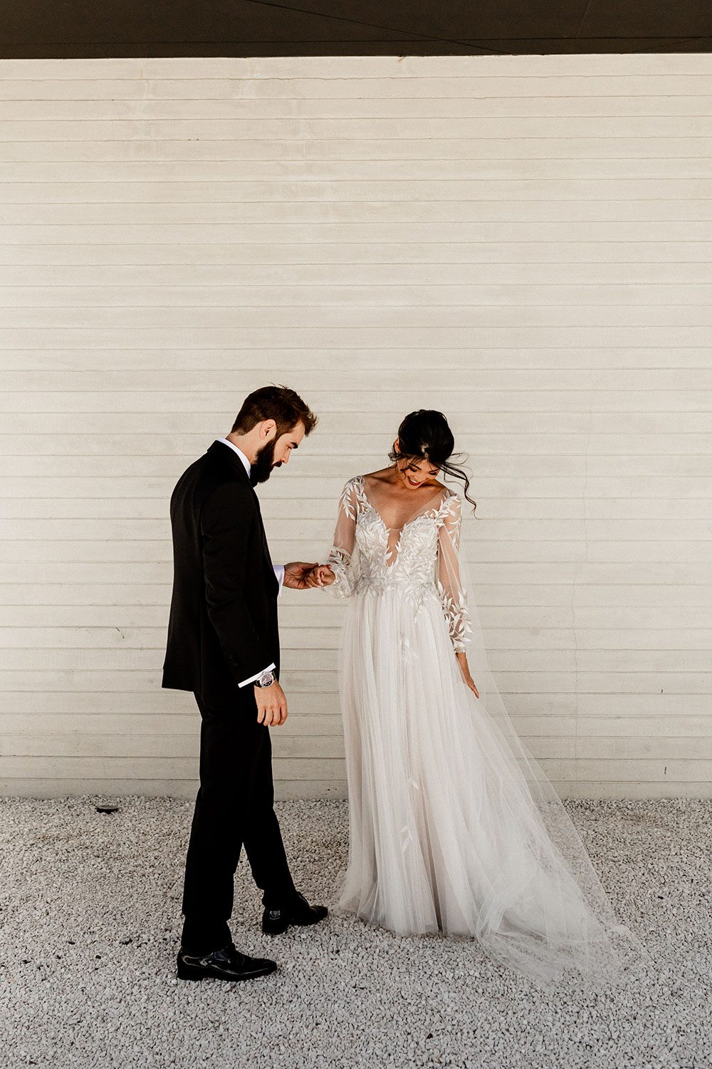 Bride wearing bespoke designer wedding dress by Vinka Bridal Boutique NZ, adorned with delicate applique lace and puffed sleeves - with groom near wall