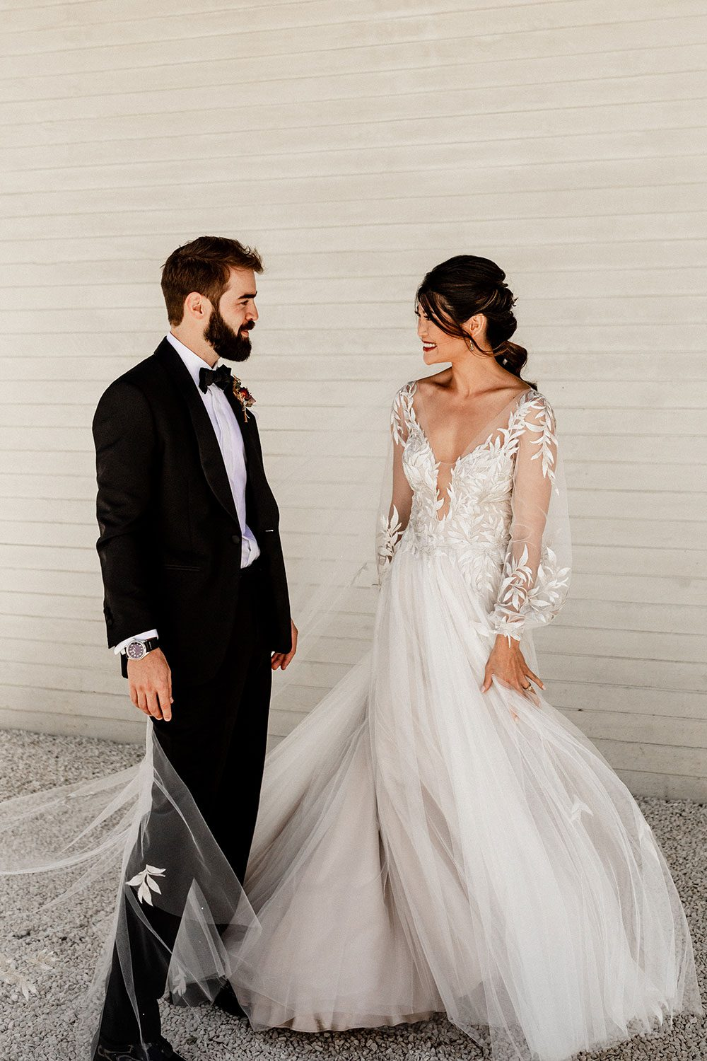 Bride wearing bespoke designer wedding dress by Vinka Bridal Boutique NZ, adorned with delicate applique lace and puffed sleeves - facing groom near wall
